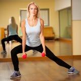 Η κατάλληλη γυναίκα επιλύει στη γυμναστική που κάνει lunge το βήμα Στοκ Εικόνα