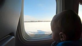 Η κατάπληξη του ξανθού μικρού παιδιού κάθεται κοντά στο παράθυρο αερο φιλμ μικρού μήκους