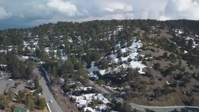 Η καταπληκτική εναέρια άποψη του τοπίου με τα βουνά κάλυψε το χιόνι και το δρόμο με τα αυτοκίνητα απόθεμα βίντεο