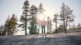 Η καταπληκτική χαμηλή γωνία που πυροβολείται του νεαρού άνδρα που στέκεται μόνο στο μεγάλο βράχο με τον ήλιο backlight καίγεται σ απόθεμα βίντεο