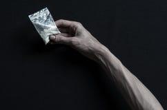 Η καταπολέμηση των ναρκωτικών και του θέματος εθισμού στα ναρκωτικά: ο εξαρτημένος χεριών βρίσκεται σε έναν σκοτεινό πίνακα και γ στοκ φωτογραφία