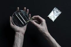 Η καταπολέμηση των ναρκωτικών και του θέματος εθισμού στα ναρκωτικά: ο εξαρτημένος χεριών βρίσκεται σε έναν σκοτεινό πίνακα και γ στοκ φωτογραφίες με δικαίωμα ελεύθερης χρήσης
