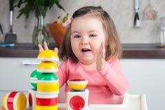 Η κατασκευή που ένα 2χρονο κορίτσι με τα μακρυμάλλη παιχνίδια με έναν σχεδιαστή στο σπίτι, χτίζει τους πύργους, χαίρεται για τις  στοκ φωτογραφία με δικαίωμα ελεύθερης χρήσης