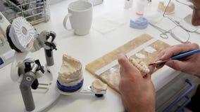 Η κατασκευή της οδοντικής πρόσθεσης για τους ασθενείς, ειδικό άτομο στα γυαλιά λερώνει το σμάλτο στα τεχνητά δόντια στον εργασιακ απόθεμα βίντεο