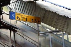 Η κατεύθυνση πινάκων και πλατφορμών κατεύθυνσης εξόδων επιβιβάζεται πέρα από ένα σκαλοπάτι μιας πλατφόρμας σιδηροδρόμων στοκ φωτογραφία με δικαίωμα ελεύθερης χρήσης