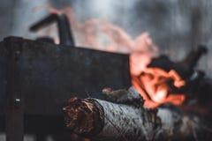 Η κατσαρόλα στέκεται κοντά στην πυρκαγιά, που θερμαίνεται για το τσάι ή τον καφέ στοκ εικόνες