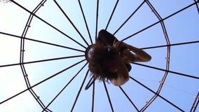Η κατώτατη άποψη ως εύκαμπτο brunette κάνει το σπάγγο στον αέρα, εναέριο acrobatics φιλμ μικρού μήκους