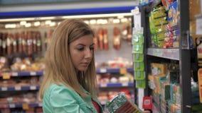 Η καυκάσια γυναίκα επιλέγει τις καθαρίζοντας προμήθειες στα ράφια στην υπεραγορά 4k απόθεμα βίντεο
