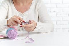 Η καυκάσια γυναίκα πλέκει τα μάλλινα ενδύματα Κράτημα των πλέκοντας βελόνων στα χέρια Στοκ φωτογραφία με δικαίωμα ελεύθερης χρήσης