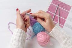 Η καυκάσια γυναίκα πλέκει τα μάλλινα ενδύματα Κράτημα των πλέκοντας βελόνων στα χέρια Στοκ Φωτογραφία