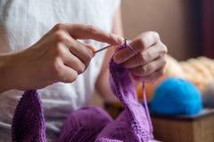 Η καυκάσια γυναίκα πλέκει τα μάλλινα ενδύματα Κράτημα των πλέκοντας βελόνων στα χέρια Στοκ Εικόνα
