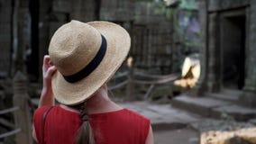 Η καυκάσια γυναίκα στο καπέλο αχύρου περπατά μεταξύ των καταστροφών του TA Prohm απόθεμα βίντεο