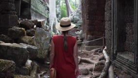 Η καυκάσια γυναίκα στο κόκκινο φόρεμα περπατά μεταξύ των καταστροφών του TA Prohm φιλμ μικρού μήκους