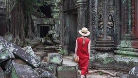 Η καυκάσια γυναίκα στο κόκκινο φόρεμα περπατά μεταξύ των καταστροφών του TA Prohm απόθεμα βίντεο
