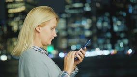 Η καυκάσια μέσης ηλικίας γυναίκα χρησιμοποιεί ένα smartphone στο υπόβαθρο των φω'των του Μανχάταν απόθεμα βίντεο