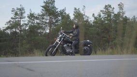 Η καυκάσια συνεδρίαση κοριτσιών στη μοτοσικλέτα της και φορά ένα κράνος και τα γάντια Γυναίκα ικανότητας σε ένα μαύρο σακάκι δέρμ φιλμ μικρού μήκους