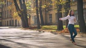 Η καυκάσια όμορφη γυναίκα μήκους σε πόδηα είναι χορεύοντας δημόσια θέση μόνη, ευτυχής και εμπνεσμένη, άποψη πόλεων, Sunshines και απόθεμα βίντεο