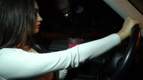 Η καυτή γυναίκα με το κόκκινο κραγιόν, οδηγεί ένα αυτοκίνητο τη νύχτα και το ρουφώντας γουλιά γουλιά καφέ απόθεμα βίντεο