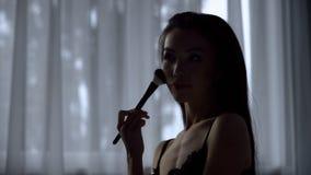 Η καυτή γυναίκα χρησιμοποιεί παιχνιδιάρικα makeup τη βούρτσα στο σώμα της, που διενεργεί τις τελικές προσαρμογές στοκ φωτογραφίες