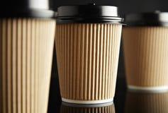 Η καφετιά πολυτέλεια παίρνει μαζί τα φλυτζάνια εγγράφου καθορισμένα μαύρο που αντανακλάται Στοκ φωτογραφία με δικαίωμα ελεύθερης χρήσης