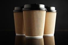Η καφετιά πολυτέλεια παίρνει μαζί τα φλυτζάνια εγγράφου καθορισμένα μαύρο που αντανακλάται Στοκ εικόνα με δικαίωμα ελεύθερης χρήσης