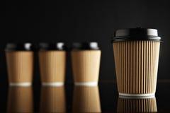 Η καφετιά πολυτέλεια παίρνει μαζί τα φλυτζάνια εγγράφου καθορισμένα μαύρο που αντανακλάται Στοκ Εικόνες