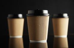 Η καφετιά πολυτέλεια παίρνει μαζί τα φλυτζάνια εγγράφου καθορισμένα μαύρο που αντανακλάται Στοκ Φωτογραφίες