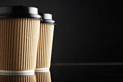 Η καφετιά πολυτέλεια παίρνει μαζί τα φλυτζάνια εγγράφου καθορισμένα μαύρο που αντανακλάται Στοκ εικόνες με δικαίωμα ελεύθερης χρήσης