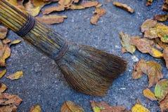 Η καφετιά σκούπα σκουπίζει επάνω στα πεσμένα ξηρά φύλλα στην άσφαλτο στοκ εικόνα