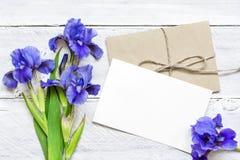 Η κενή άσπρη ευχετήρια κάρτα με την μπλε ίριδα ανθίζει την ανθοδέσμη και το φάκελο Στοκ Φωτογραφίες