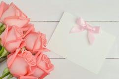 Η κενή ευχετήρια κάρτα με το ρόδινο τόξο κορδελλών και ρόδινος αυξήθηκε λουλούδια Στοκ φωτογραφία με δικαίωμα ελεύθερης χρήσης