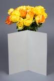 Η κενή κάρτα δώρων και η όμορφη ανθοδέσμη πορτοκαλής και κίτρινος αυξήθηκαν Στοκ Φωτογραφία
