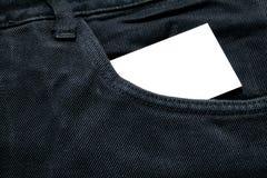 Η κενή Λευκή Βίβλος ή κάρτα στην μπροστινή τσέπη των μαύρων τζιν με το copyspace για την έννοια κειμένων ή επιχειρήσεων πώλησης στοκ φωτογραφίες