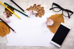 Η κενή Λευκή Βίβλος για τον ξύλινο πίνακα με τα μολύβια χρώματος, το κινητό τηλέφωνο, τα γυαλιά και το φθινόπωρο φεύγει Στοκ Φωτογραφία