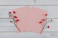 Η κενή ροζ κάρτα δύο διακοσμεί με τα κόκκινα λουλούδια εγγράφου Στοκ Φωτογραφίες