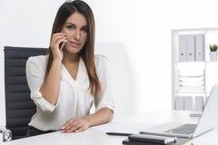 Η κεντροθετημένη επιχειρηματίας με την καφετιά τρίχα είναι στο τηλέφωνό της Στοκ εικόνα με δικαίωμα ελεύθερης χρήσης