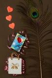 Η κεραμική τσάντα, κιβώτιο με το δώρο ημέρας βαλεντίνων, peacock επενδύει με φτερά και τρεις κόκκινες καρδιές Στοκ Φωτογραφία