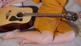 Η κιθάρα είναι στα πόδια του κοριτσιού απόθεμα βίντεο