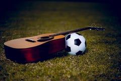 Η κιθάρα και το ποδόσφαιρο τοποθετούνται στους πράσινους χορτοτάπητες Μουσική και αθλητισμός στοκ φωτογραφίες