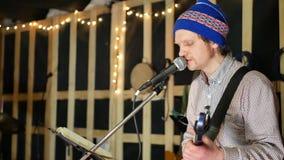 Η κιθάρα παιχνιδιού κιθαριστών μολύβδου ατόμων και τραγουδά το τραγούδι απόθεμα βίντεο