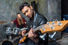 Η κιθάρα παιχνιδιού ανδρών με τα τύμπανα παιχνιδιού γυναικών, βράχος - και - κυλά την έννοια ζωνών Στοκ Εικόνα