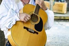 Η κιθάρα που κατέχει το άτομο στο ιστορικό άσπρο πουκάμισο αγροτών με το αγροτικό στάδιο θόλωσε στο υπόβαθρο στοκ φωτογραφίες