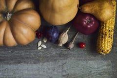 η κινηματογράφηση σε πρώτο πλάνο ανασκόπησης φθινοπώρου χρωματίζει το φύλλο κισσών πορτοκαλί Κολοκύθα, μήλο, καλαμπόκι στο ξύλινο Στοκ Φωτογραφίες