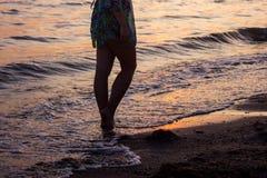 Η κινηματογράφηση σε πρώτο πλάνο γυμνών ποδιών ενός κοριτσιού που περπατά στην παραλία στο ηλιοβασίλεμα, με μια άκρη κυμάτων, που Στοκ φωτογραφία με δικαίωμα ελεύθερης χρήσης