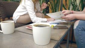 Η κινηματογράφηση σε πρώτο πλάνο, γυναίκες ` s παραδίδει τα έγγραφα σημαδιών καφέδων Επιχειρησιακή συνεδρίαση σε έναν καφέ στοκ εικόνες