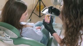 Η κινηματογράφηση σε πρώτο πλάνο ενός επιβραδυνμένου πυροβολισμού το των οδοντιάτρων γυναικών ` s, ένας οδοντίατρος, εξηγεί στον  απόθεμα βίντεο