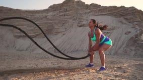 Η κινηματογράφηση σε πρώτο πλάνο ενός κοριτσιού με ένα σχοινί διευθύνει την υπαίθρια κατάρτιση στο αμμώδες έδαφος κοντά στην παρα απόθεμα βίντεο