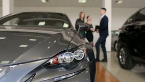 Η κινηματογράφηση σε πρώτο πλάνο ενός νέου αυτοκινήτου στην αίθουσα εκθέσεως, στους ανθρώπους υποβάθρου επιλέγει ένα αυτοκίνητο φιλμ μικρού μήκους