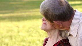 Η κινηματογράφηση σε πρώτο πλάνο ενός παππού φιλά τη σύζυγό του στο πάρκο απόθεμα βίντεο