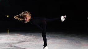 Η κινηματογράφηση σε πρώτο πλάνο ενός σκέιτερ κοριτσιών στον πάγο πραγματοποιεί μια περιστροφή γύρω από τον άξονά της στεμένος στ απόθεμα βίντεο